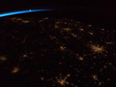 The Moon rising above Earth at night