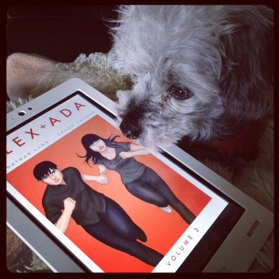A sleek grey poodle, Murchie, sticks his chin over a white Kobo with the cover of Alex + Ada Volume 3 on its screen. The cover features a pale-skinned woman and man running straight at the viewer. They hold hands and wear dark clothes. The background is brilliant orange.