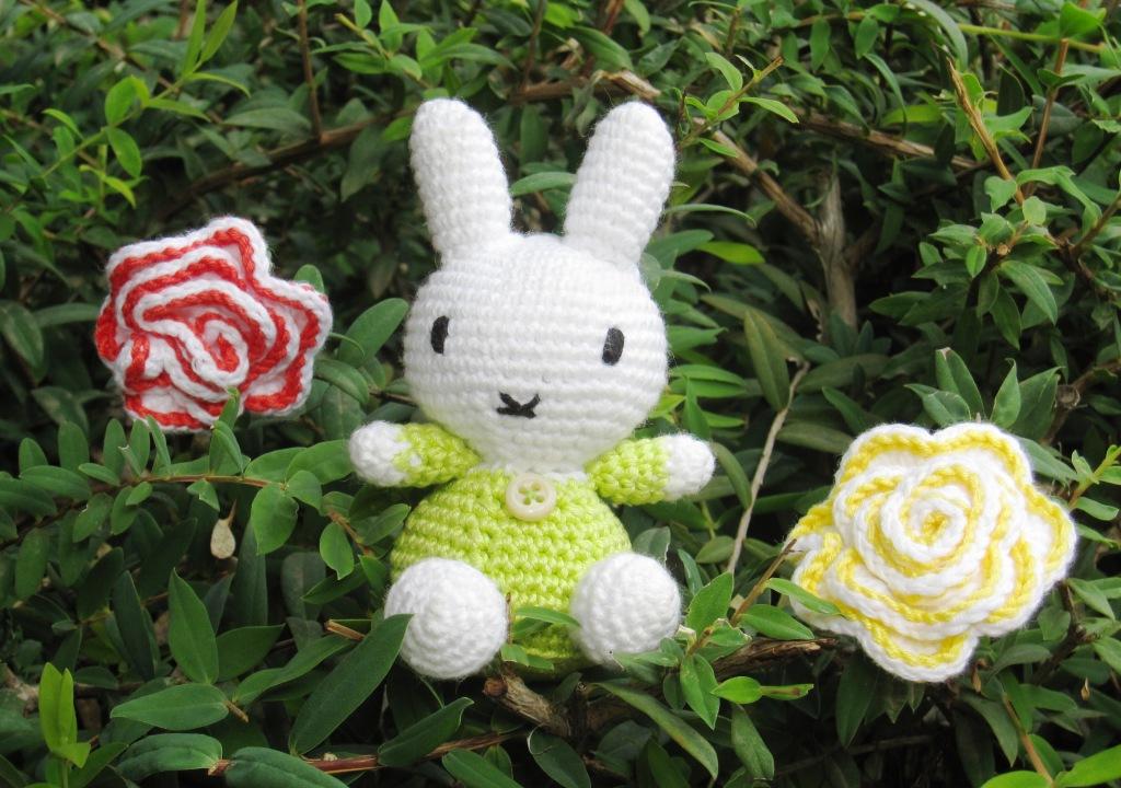 Detalle del Conejito estilo Miffy en el jardín junto a dos flores
