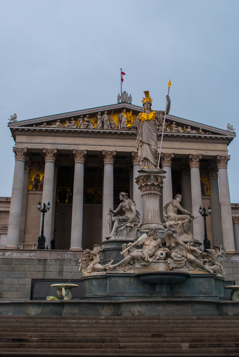 The statues and structures in front of the parliament house in Vienna, Austria in the rain