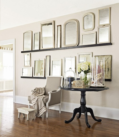 different shapes and sized mirrors on floating shelves mounted on a wall as art in a hallway