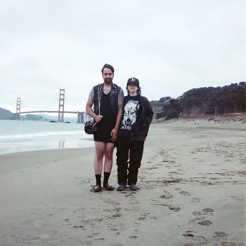 Esta foto é no mesmo lugar que a anterior, porém o casal trocou as roupas. Ele veste a saia e bolsa, enquanto ela está e chapéu e uma jaqueta de couro imensa para ela.