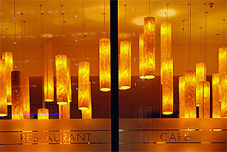 orange lamps hanging in restaurant viewed through window 