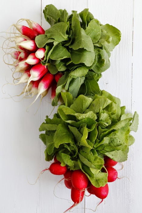 2 bunches of radishes on a white wooden background