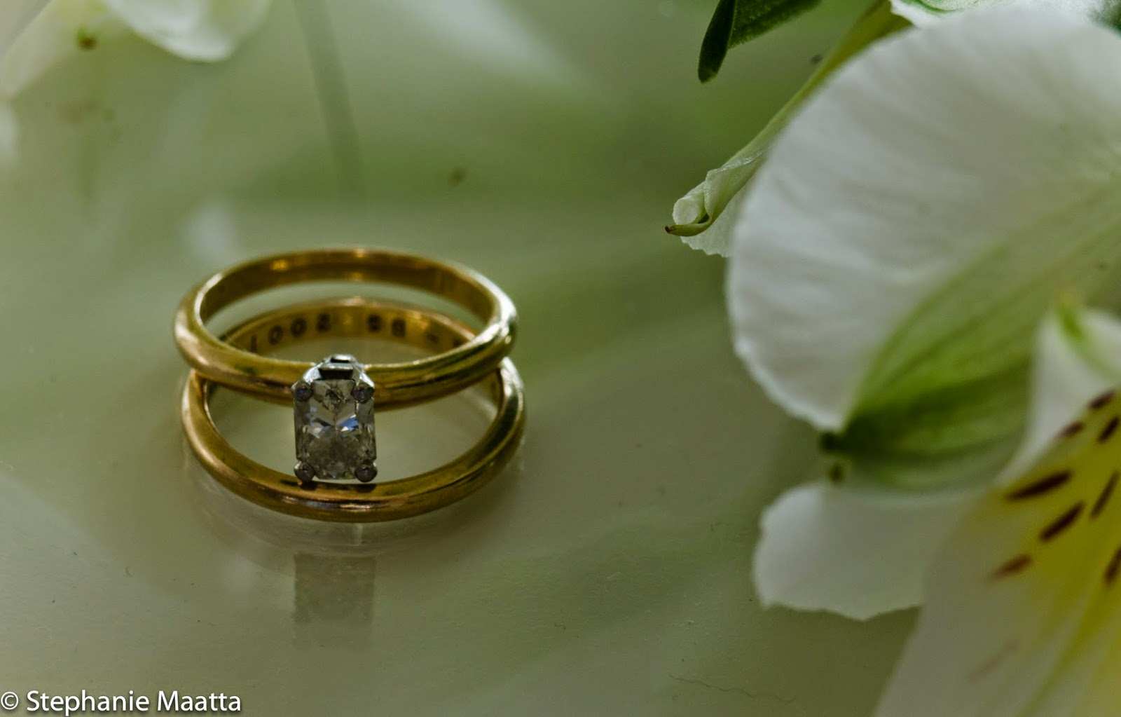 image of wedding and engagement rings with white flowers