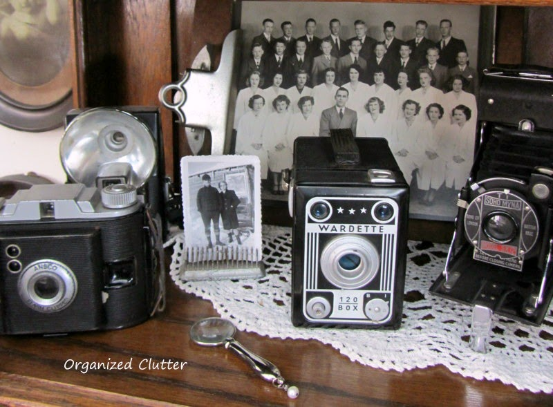 Cameras Displayed in China Cabinet www.organizedclutterqueen.blogspot.com