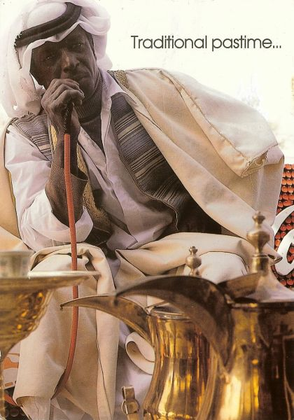 man in white robes smoking a hookah