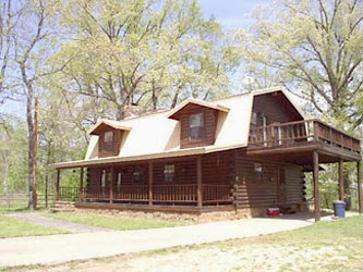 ... Lower Mountain Fork River. White Roofed Two Story Log Cabin Surrounded  By Trees