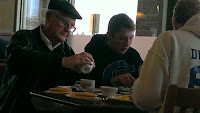 Elderly man with two youth eating breakfast at a restaurant.