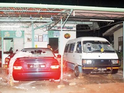 Kereta dan van di luar rumah jiran mangsa yang rosak berikutan kes itu.