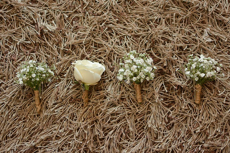 buttonholes for the groom; white rose, baby's breaths