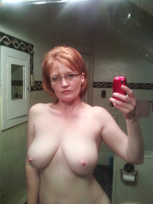 Horny older MILF takes a naked picture of herself in the bathroom mirror, showing off those big mommy tits and very suckable pink nipples.