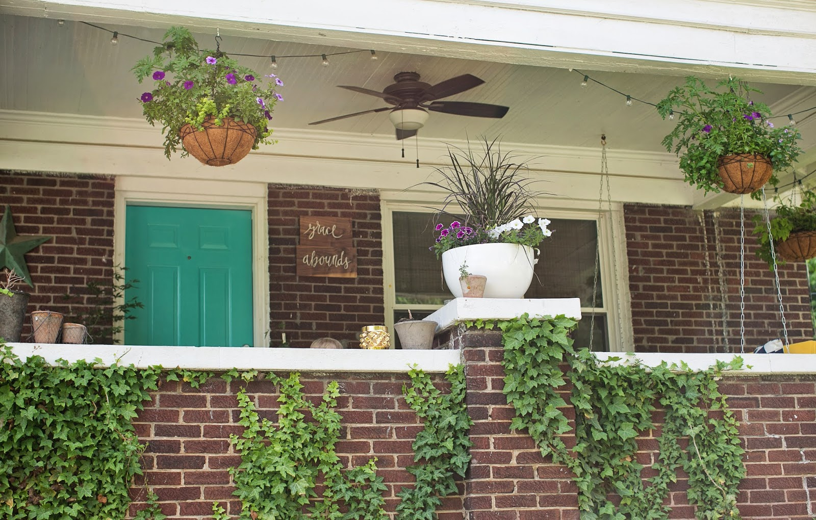 front porch makeover with bright blue door and yellow swing and hanging baskets