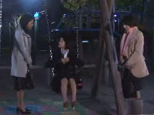 Misaki sits on a swing while speaking with Wakamura and Sekiyama.
