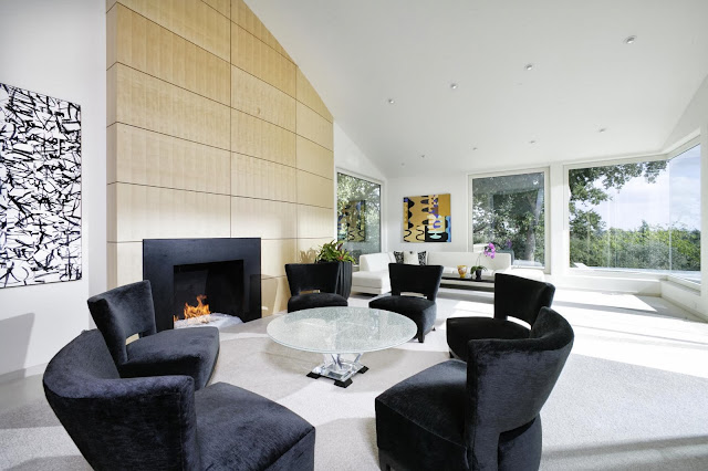open plan space covering black circular lounge by the fireplace, white lounge area and view to the lush garden