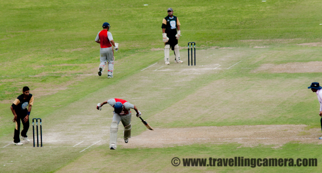 T20 Cricket Mahasangram - A Cricket Tournament that broke World Records : Postd by VJ SHARMA on www.travellingcamera.com : The Jaypee Twenty20 Mahasangram has made into the Guiness Book of World Records as the world's largest cricket tournaments. The statistics it boasts of are unbelievable. Consider the following: A total of 1,406 teams, 19,684 players, near about 2000 matches, 77 grounds on which 150 matches were played daily.I had never heard of anything like this before. And when I did hear about it, I could not resist attending the final match of the tournament. The match was also attended by Mr. Anurag Thakur, MP Lok Sabha who is also the President of Himachal Pradesh Cricket Association and a Member of the IPL Governing Coucil.This is the cricket stadium of Dharamshala situated height of 1,457 m above the sea level. With such beautiful backdrop, how do players manage to concentrate on the game? Even the stalls are so pretty. More matches should be played here. During this event, it came to know that 3 matches of upcoming IPL will be played in this beautiful Stadium...Here are the HPCA and Jaypee officials talking to media. A tournament of the size of Jaypee Twenty20 Mahasangram takes a lot of courage and co-ordination to organize. These men and their teams have been instrumental in taking the cricket scene in Himachal Pradesh to greater heights.Here is one of the finalists, the team from Mandi posing for a photograph with Mr.Anurag Thakur. I love their uniforms. I did not know red and grey could look so good together. The second finalist was the team from Una.Mandi team got to bowl first. Here is there wicket keeper grasping the ball.Here is a batsman from team Una walking back to the pavilion after being given out. Notice the dress again. Excellent combination. I think a few of the international teams can learn from the designers of these dresses.Another batsman going back to the pavilion. The excitement was increasing with each passing minute. This is the a