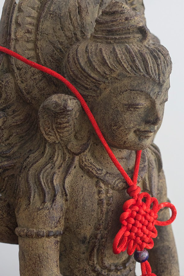 Indian deity with red ribbon