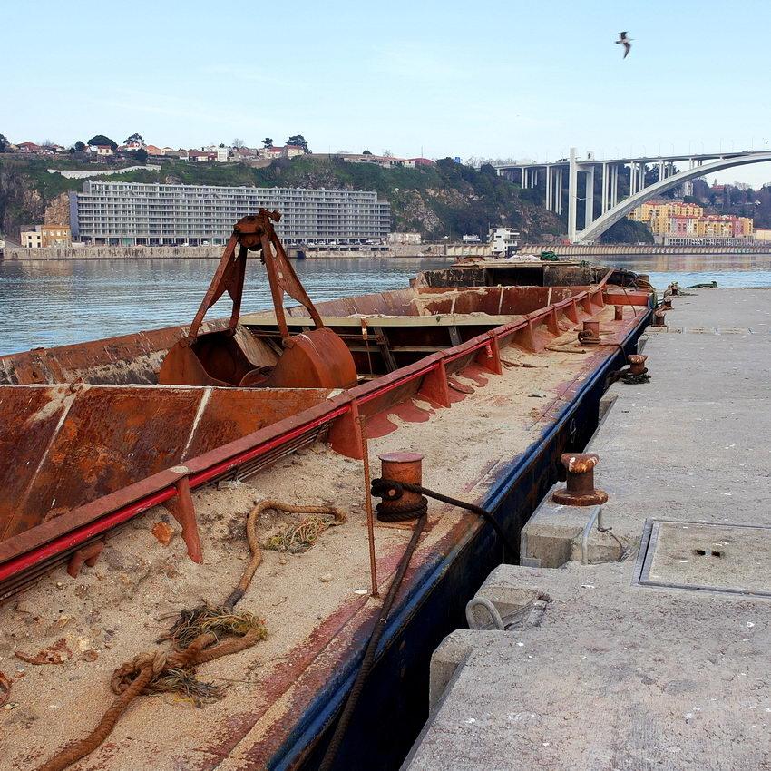 Foto de um batelão de areia ancorado. Ao fundo a ponte da Arrábida e a margem do lado da cidade do Porto. Uma gaivota cruza o céu