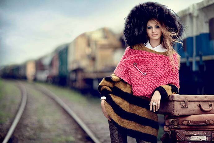 A model wearing oversized striped knitted sweater, pink chunky knitted scarf and a big furry hat
