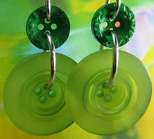Green drop dangle earrings have constrasting big bright buttons hanging from smaller dark buttons