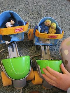 Dollhouse people in a rollerskate car.
