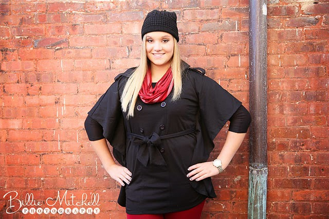 blonde teen girl wearing black jacket and hat, red scarf, standing in front of brick wall