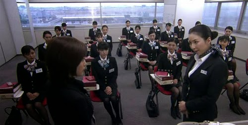 Mikami speaks to Misaki in front of a classroom of trainees.