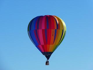 Fotografía de un globo aerostático de colores volando en el cielo