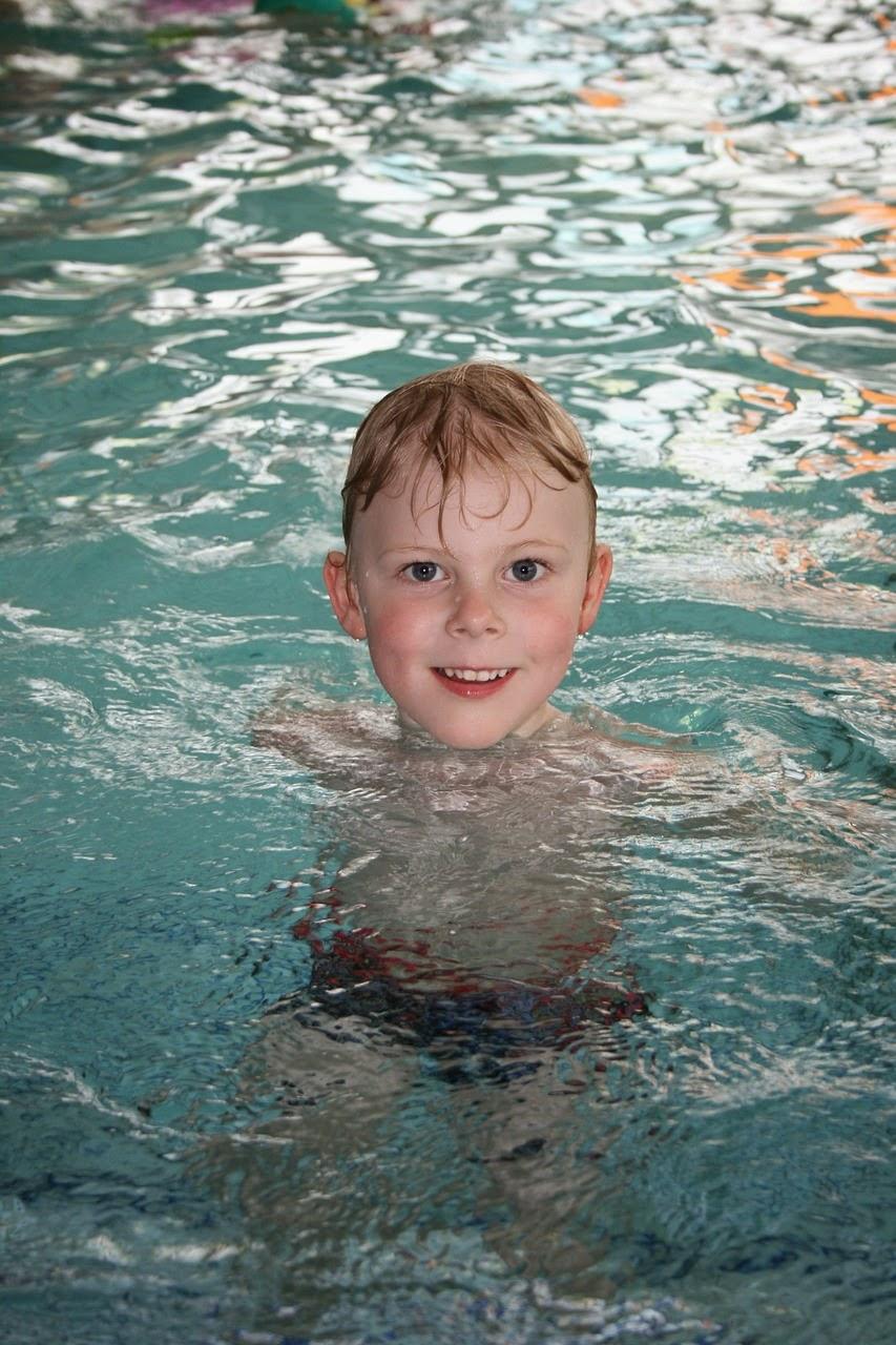 Junge schwimmt im Hallenbad