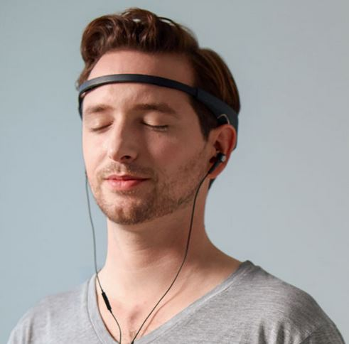 A young man meditates with Muse, a brain-sensing headband, and his headphones.