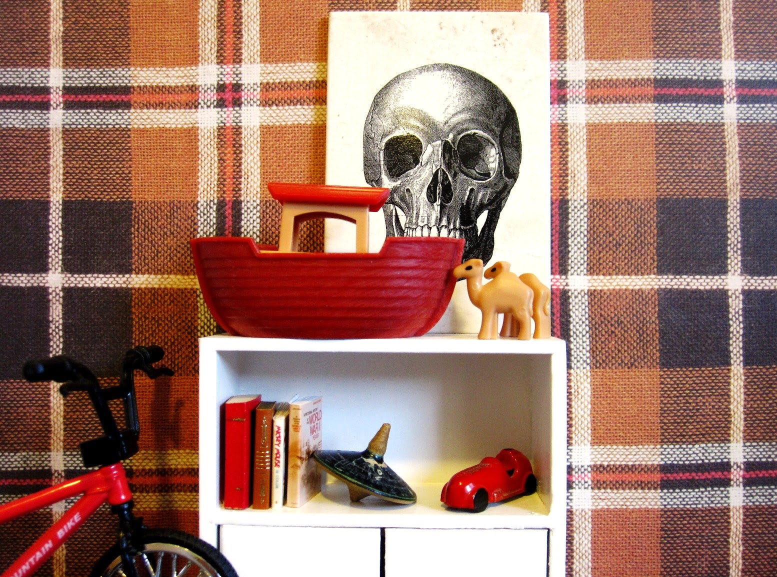 Modern dolls' house scene of part of a boy's room, with fawn, red and white tartan wallpaper and a white shelf holding a Noah's ark, a toy car, some books and a spinning top. To one side is a BMX-style bike.