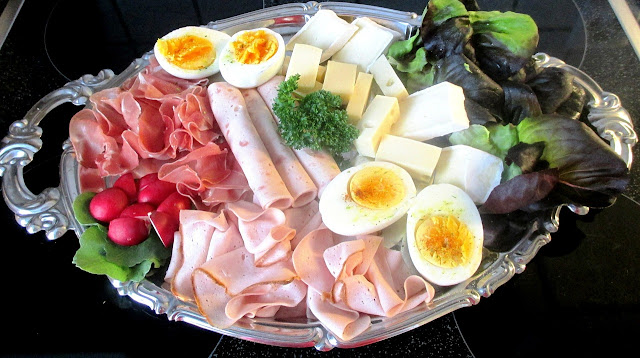Silver tray of cold cuts, deviled eggs, cheese, and radishes
