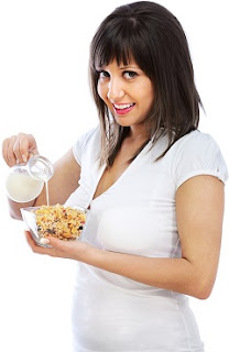 smiling-brunette-pouring-milk-on-cereal