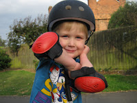 boy in bike protection gear hat and arm pads