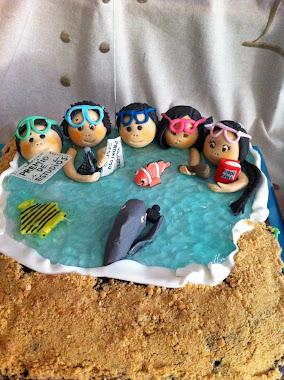 tarta de buceadores y tiburón, en playa con el mar.