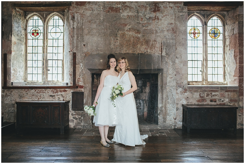 Two brides standing by fireplace in the Great Hall at St Nicholas Priory