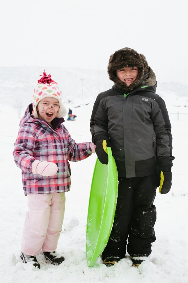 brother and sister posing for a photograph in the snow