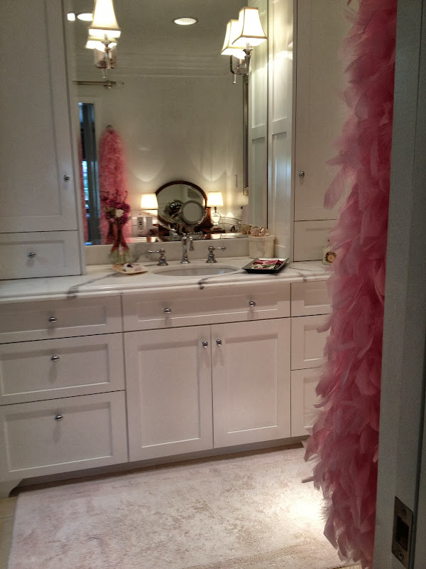 Feminine touch to this all white bathroom is just a pink boa title=