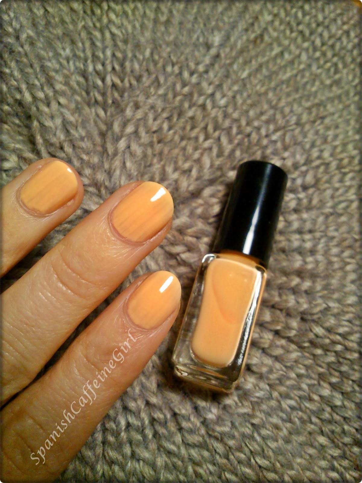uñas con dos capas de esmalte naranja muy claro