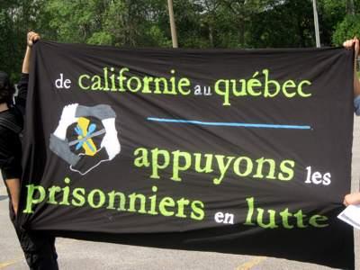bannière tenue tendue pour la photo: de la Californie au Québec, appuyons les prisonniers en lutte