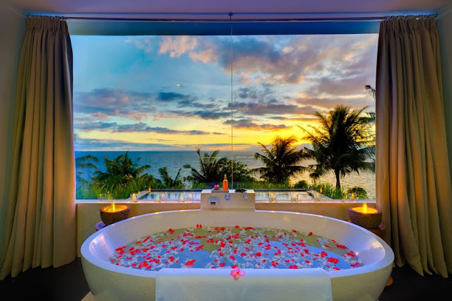 Picture of the ocean at sunset as seen from the bedroom with the bathtub by the window