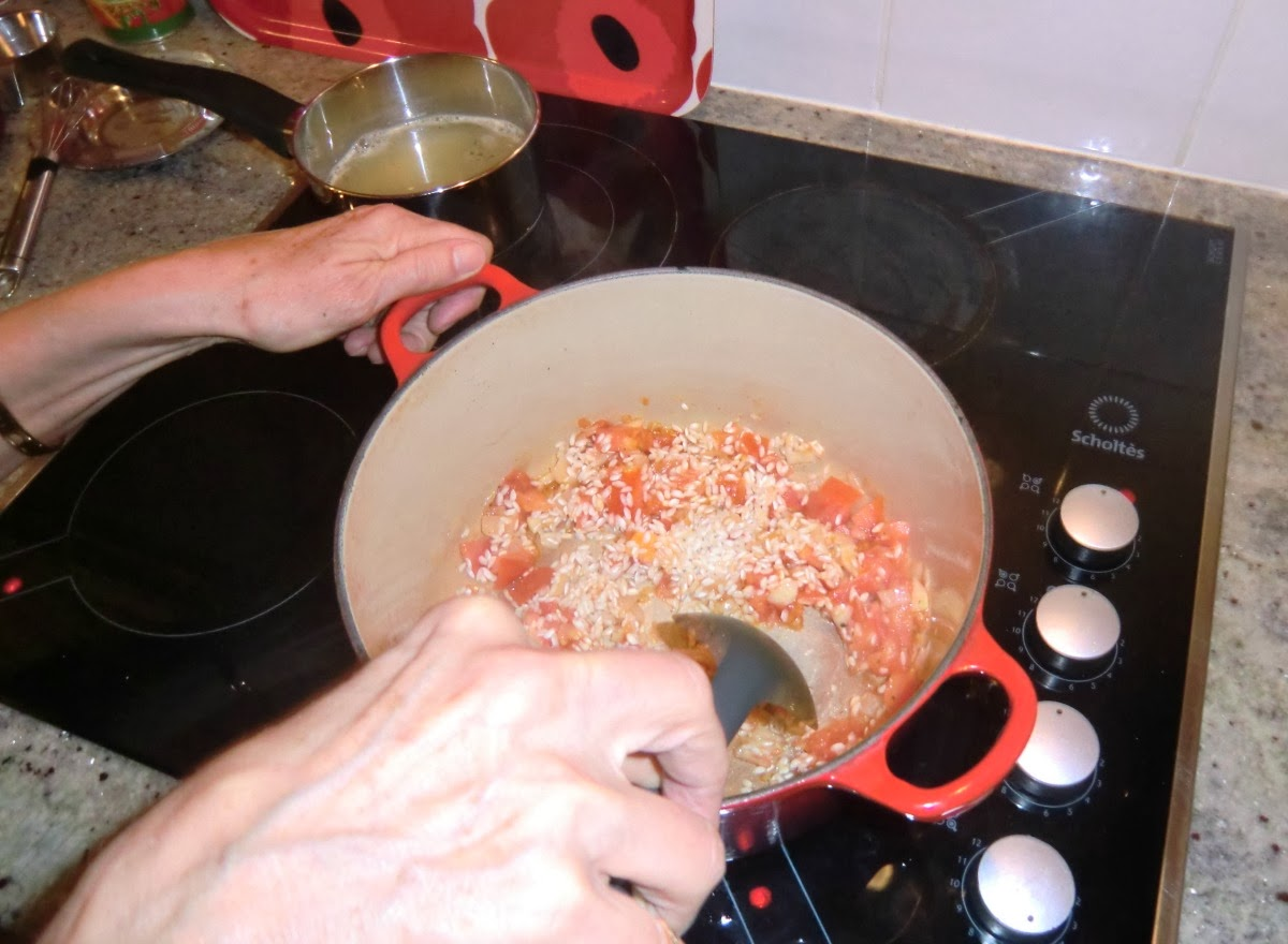 Stirring the risotto rice in the casserole and mixing with the oil and vegetables