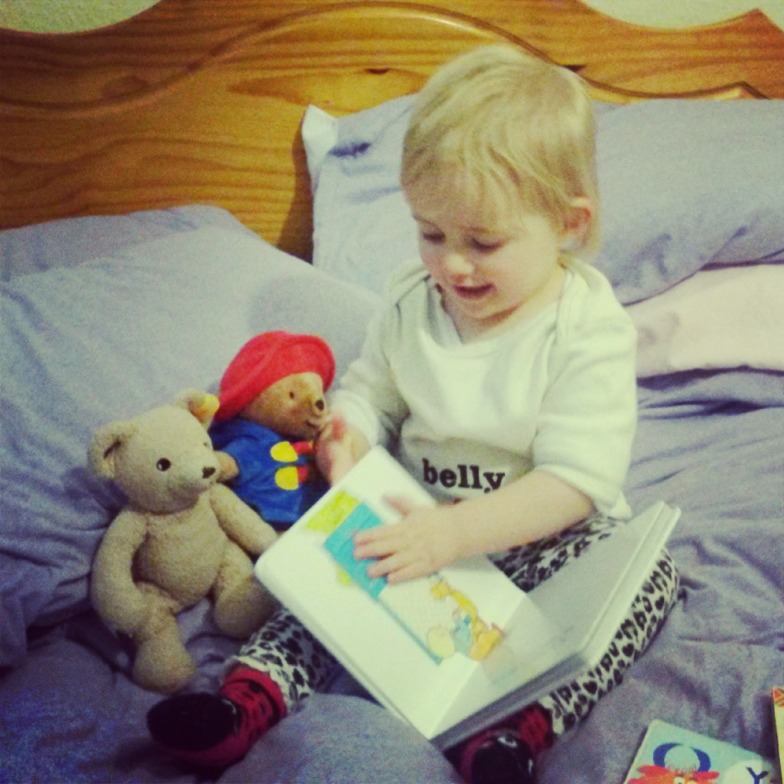 Toddler reading story to Paddington and teddy