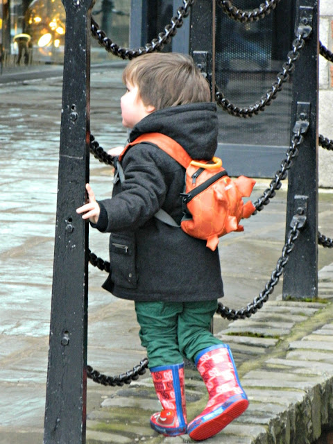 Bud exploring small boy toddler Liverpool Albert Dock wellies