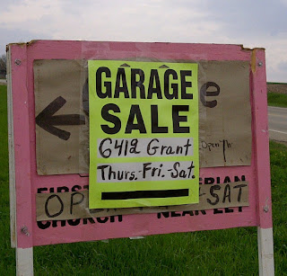Printed garage sale sign with address and days of sale written in marker