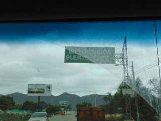 """<div>Driving from Cartagena, Colombia, to the border of Ecuador was relatively uneventful. Once we got off the Ruta Caribe (Carribean Road), we were reminded to fasten our seatbelts and not drink and drive.<p></p></div><div><br /></div><div><a href=""""http://1.bp.blogspot.com/-KGxG9XRdHdM/Vl4-MUbpGQI/AAAAAAAABTU/lRAF_dkVX-0/s1600/DSC00602.JPG""""><img border=""""0"""" height=""""240"""" src=""""http://1.bp.blogspot.com/-KGxG9XRdHdM/Vl4-MUbpGQI/AAAAAAAABTU/lRAF_dkVX-0/s320/DSC00602.JPG"""" width=""""320""""/></a></div><div><br /></div><div>I also loved they the Colombians let you know of points of interest nearby.<p></p></div><br /><div><a href=""""http://3.bp.blogspot.com/--FPz0npDL5I/Vl4-YNatZAI/AAAAAAAABTc/MFrt79N7x3E/s1600/DSC00609.JPG""""><img border=""""0"""" height=""""240"""" src=""""http://3.bp.blogspot.com/--FPz0npDL5I/Vl4-YNatZAI/AAAAAAAABTc/MFrt79N7x3E/s320/DSC00609.JPG"""" width=""""320""""/></a></div><div><br /></div><div>And, hitchhikers are always able to find a ride! This is a container on a car hauler with two guys on the back. This was not an uncommon combination!<p></p></div><br /><div><a href=""""http://4.bp.blogspot.com/-iFktt8r3NXY/Vl4-fB3-geI/AAAAAAAABTk/xEvVMS9Fz0k/s1600/DSC00610.JPG""""><img border=""""0"""" height=""""240"""" src=""""http://4.bp.blogspot.com/-iFktt8r3NXY/Vl4-fB3-geI/AAAAAAAABTk/xEvVMS9Fz0k/s320/DSC00610.JPG"""" width=""""320""""/></a></div><div><br /></div><div>In the northern part of the country, the landscape reminded me of the area in which I grew up, except the hills were bigger and steeper. In my part of Kentucky, the hillsides tended to be dotted with cattle, predominantly Holstein. Sometimes, those cattle dotted the road, too. (At least ours did!)</div><div><p></p></div><div><br /></div><div>We were also driving up and down hills, seeing nothing other than farms and a few houses. Suddenly, there was a little town that may have a cross street, but not necessarily. These little towns all had the same makeup: A few houses, a restaurant or two, a gas station, and a little market. Every two or three towns, th"""