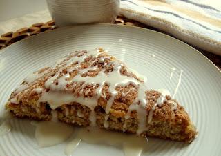 cinnamon roll scone on white plate with vanilla glaze.