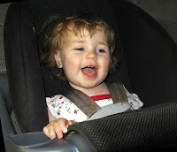 child in car seat smiling