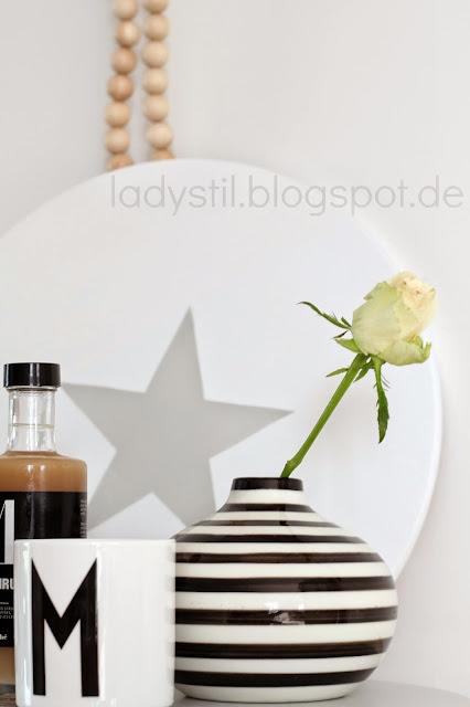 weißer Drehteller mit grauem Stern davor steht eine schwarzweiß getreifte Vase mit einer Rose und ein Designlettersbecher mit einem M