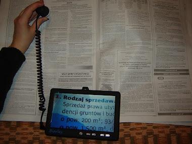 Osoba słabowidząca czyta gazetę